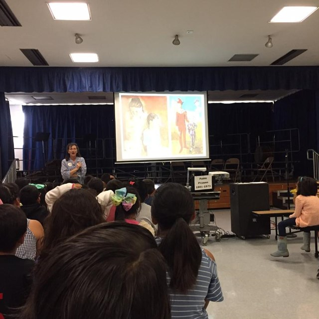 Scholars actively learn about historical paintings during the Art Assembly, embracing the importance of creativity and self-expression.